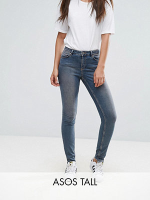 Asos Tall LISBON Medelhöga jeans med extra smal passform i Dita-tvätt med ojämn fåll bak Mellanblå färg