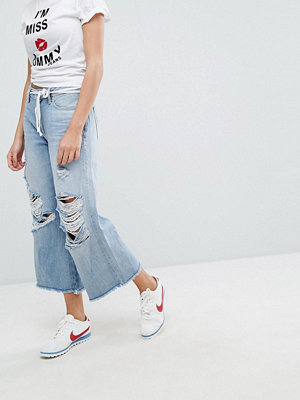 Tommy Jeans Annie Medelhöga culottebyxor med råskuren kant och revor på knäna Urtvättad denim