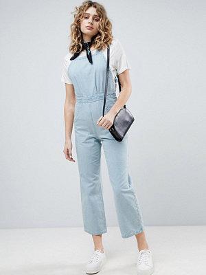 ASOS DESIGN denim cross back jumpsuit in midwash blue