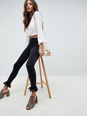 ASOS DESIGN Whitby Svarttvättade låga jeans med smal passform och tyllfåll Tvättad svart