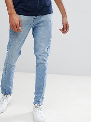 ASOS DESIGN Tall Skinny Twisted Seam Jeans In Light Wash Blue With Abrasions - Light wash blue