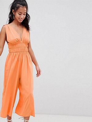ASOS Petite ASOS DESIGN Petite Ruched Waist Plunge Jumpsuit - Peach