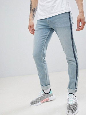 ASOS DESIGN skinny jeans in light wash blue with aztec taping - Light wash blue
