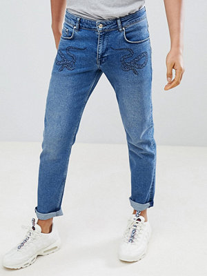 ASOS DESIGN slim jeans in mid wash blue with snake print - Mid wash blue