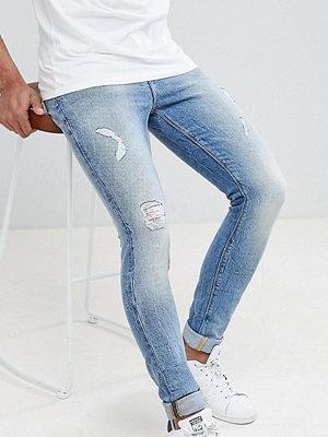 ASOS DESIGN Tall super skinny jeans in mid wash vintage blue with abrasions - Mid wash vintage