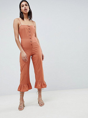 ASOS DESIGN cotton frill hem jumpsuit with square neck and button detail - Rust