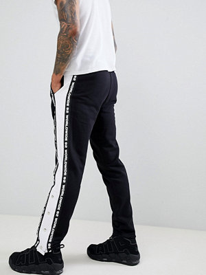 ASOS DESIGN slim joggers with taping & poppers