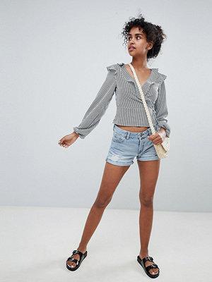 Monki Ljusblå slitna jeansshorts