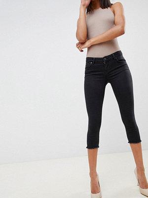 ASOS DESIGN Whitby supersmala svarttvättade jeans med låg midja i caprilängd Tvättad svart