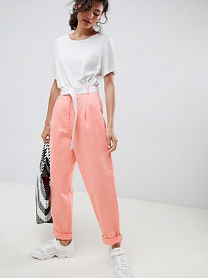 ASOS DESIGN tapered jeans with curved seams in washed neon with white belt - Washed neon orange