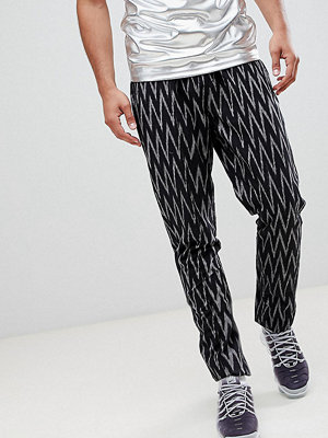 ASOS DESIGN Tall festival tapered trousers in black aztec print