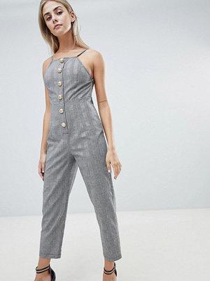 PrettyLittleThing Rutig figursydd jumpsuit med knapp framtill