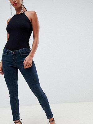 ASOS Petite Whitby Mörkblå jeans med låg midja och smal passform i dekonstruerad stil Mörk stentvättad blå
