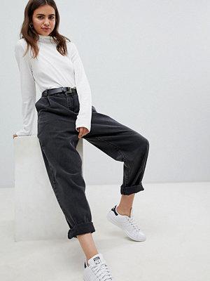 ASOS DESIGN Svarta avsmalnade jeans med uppvikt fåll oxh skärp Tvättad svart
