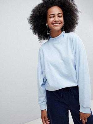 Monki Ljusblå t-shirt i oversize-modell med hög krage