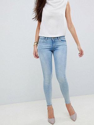 ASOS DESIGN Whitby Blå stentvättade jeans med låg midja och smal passform Lätt stentvätt