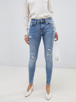 River Island Amelie Mellanblå jeans i skinny fit med slitna partier Mid auth