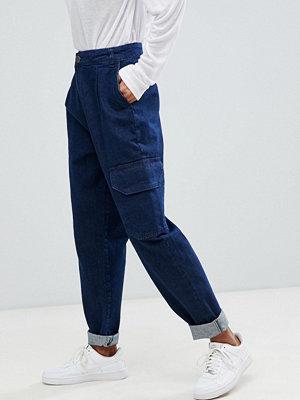 ASOS DESIGN Avsmalnande jeans i indigoblå tvätt med rundad söm och funktionsfickor Mellanblå färg