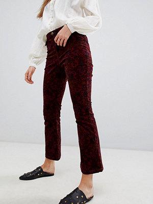 Free People Mönstrade utsvängda jeans i beskuren modell Vin