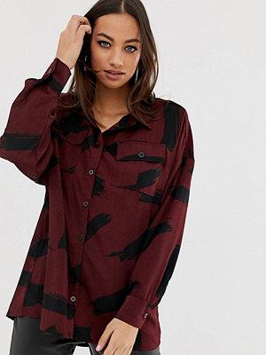 PrettyLittleThing Exclusive Skjorta med penseldragsmönster Vinröd
