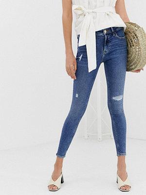River Island Amelie Mellanblå jeans med smal passform och revor Mid auth