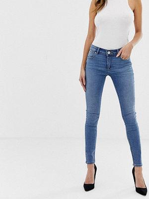 ASOS DESIGN Whitby Mellanblå skinny jeans med låg midja Mellanblå