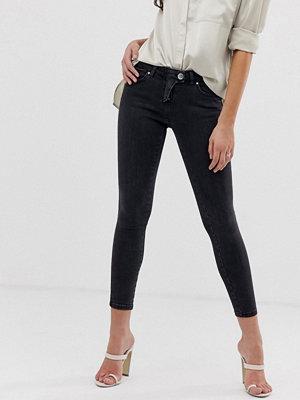 ASOS DESIGN Whitby Svarta skinny jeans med låg midja och cowboyinspirerad gylf Rensvarta