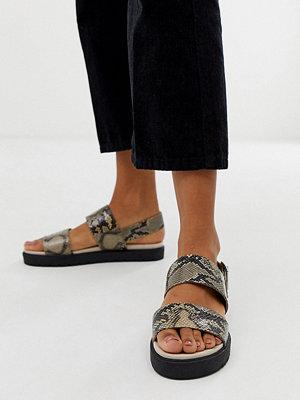 Monki Exclusive Bruna ormskinnsmönstrade platta sandaler med hälrem Ormmönster