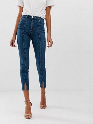 ASOS DESIGN Ridley Mellanblå skinny jeans Med sömmar framtill och slits nertill Mellanblå