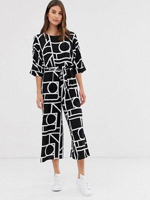 ASOS DESIGN Svartvit jumpsuit med knytning i midjan och geometriskt mönster Svartvitt geometriskt mönster