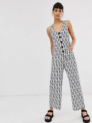 ASOS DESIGN Svart och vitmönstrad minimalistisk jumpsuit med knappar framtill Monogram-mönster