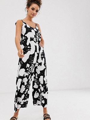 ASOS DESIGN Minimalistisk jumpsuit i svartvitt mönster med knytning baktill Svartvitt fläckmönster