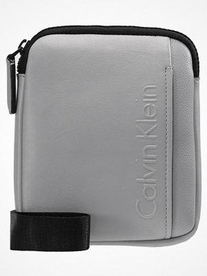 Väskor & bags - Calvin Klein ELEVATED LOGO MINI FLAT CROSSOVER Axelremsväska grey