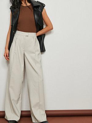 NA-KD Trend Återvunna veckade kostymbyxor med låg midja och vida ben beige