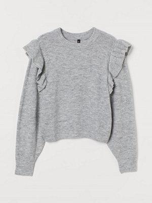 H&M Stickad tröja med volang grå