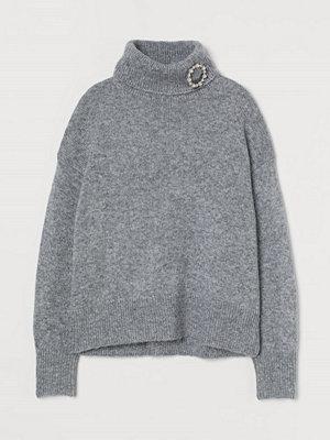 H&M Stickad polotröja med brosch grå